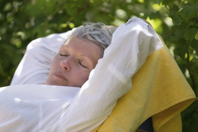 Senior woman with white hairs sleeping on lounger in her garden.
